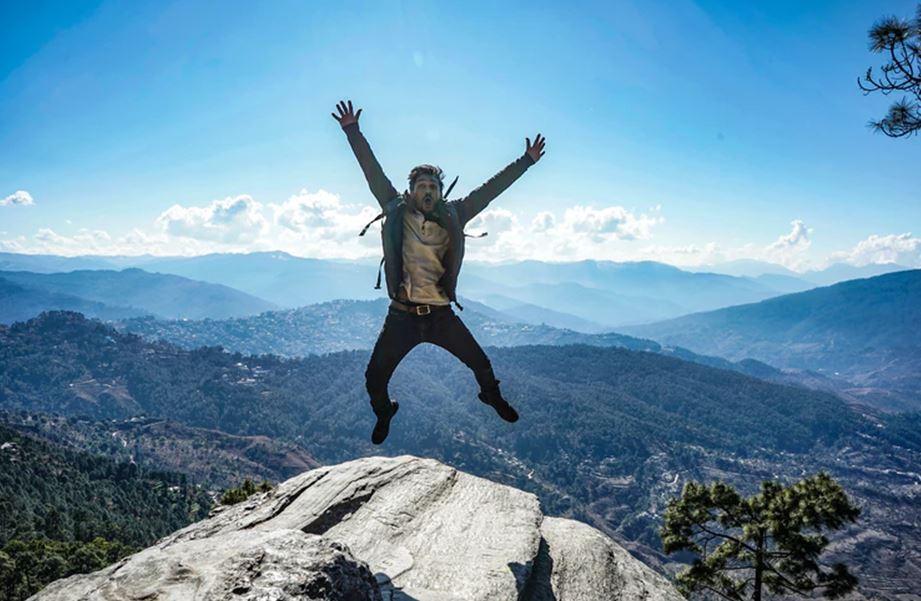man in brown jacket jumping on mountain during daytime
